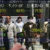 People's reflections are shown in a Tokyo stock indicator. Japan's economy is performing well and deserves more attention as a model of capitalism that manages to balance income growth and income distribution. | AP