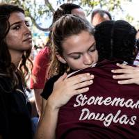 Students attend a memorial service at Marjory Stoneman Douglas High School in Parkland, Florida, on Feb. 15, a day after a mass shooting on campus that left 17 dead. | REUTERS