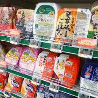 Easy eats: Different brands of microwavable rice line the shelves of a Tokyo grocery store. | KYODO