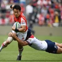 The Sunwolves' Kenki Fukuoka is tackled by Reds' fullback Hamish Stewart in Super Rugby action in Tokyo on Saturday. | AFP-JIJI