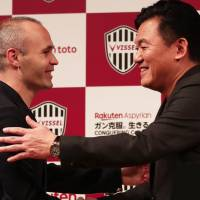 Former Barcelona star Andres Iniesta shakes hands with Vissel Kobe owner Hiroshi Mikitani at a news conference in Tokyo on Thursday. | AFP-JIJI