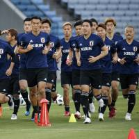 Japan national team players warm up during a training session on Tuesday at Nissan Stadium in Yokohama. Japan faces Ghana in a friendly on Wednesday. | AP