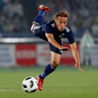 Japan's Keisuke Honda looks to keep his balance during Wednesday's international friendly against Ghana at Nissan Stadium.    REUTERS | REUTERS