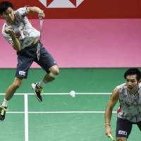 Japan's Yuta Watanabe hits a return as doubles partner Keigo Sonoda looks on during their Thomas Cup final match against China in Bangkok on Sunday. | AFP-JIJI