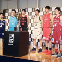 Players representing the eight teams that have made the B. League playoffs, including Yuta Tabuse of the reigning champion Tochigi Brex (second left), pose with the championship trophy on Monday. | KAZ NAGATSUKA