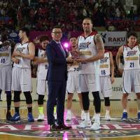 Rizing Fukuoka Zephyr star Josh Peppers, standing next to B. League chairman Masaaki Ogawa, helped carry the Kyushu-based club to the second-division championship on Sunday in Akita. | B. LEAGUE