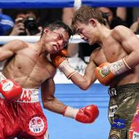 Hiroto Kyoguchi (right) lands a punch on Vince Paras of the Philippines during their IBF minimumweight title fight on Sunday. | KYODO