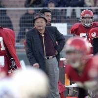 Former Nihon University head coach Mikio Shinotake watches from the sideline as his team takes on Rikkyo University during a December 2001 game. | KYODO