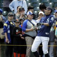 Ichiro Suzuki, laughing as Mariners fans stand near the field before Sunday's game in Seattle, will serve as the team's bench coach this weekend. | AP