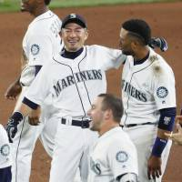 Seattle's Ichiro Suzuki celebrates with teammate Robinson Cano after the Mariners' walk-off win over the Angels on Saturday in Seattle. | KYODO