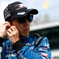 Takuma Sato adjusts his earpiece prior to his qualification attempt on May 19 at Indianapolis Motor Speedway. | JOE SKIBINSKI