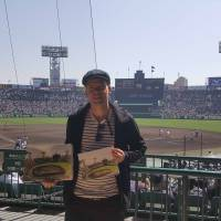 Andy Brown poses with his paintings during the National High School Baseball Tournament at Koshien Stadium last year. | COURTESY OF ANDY BROWN