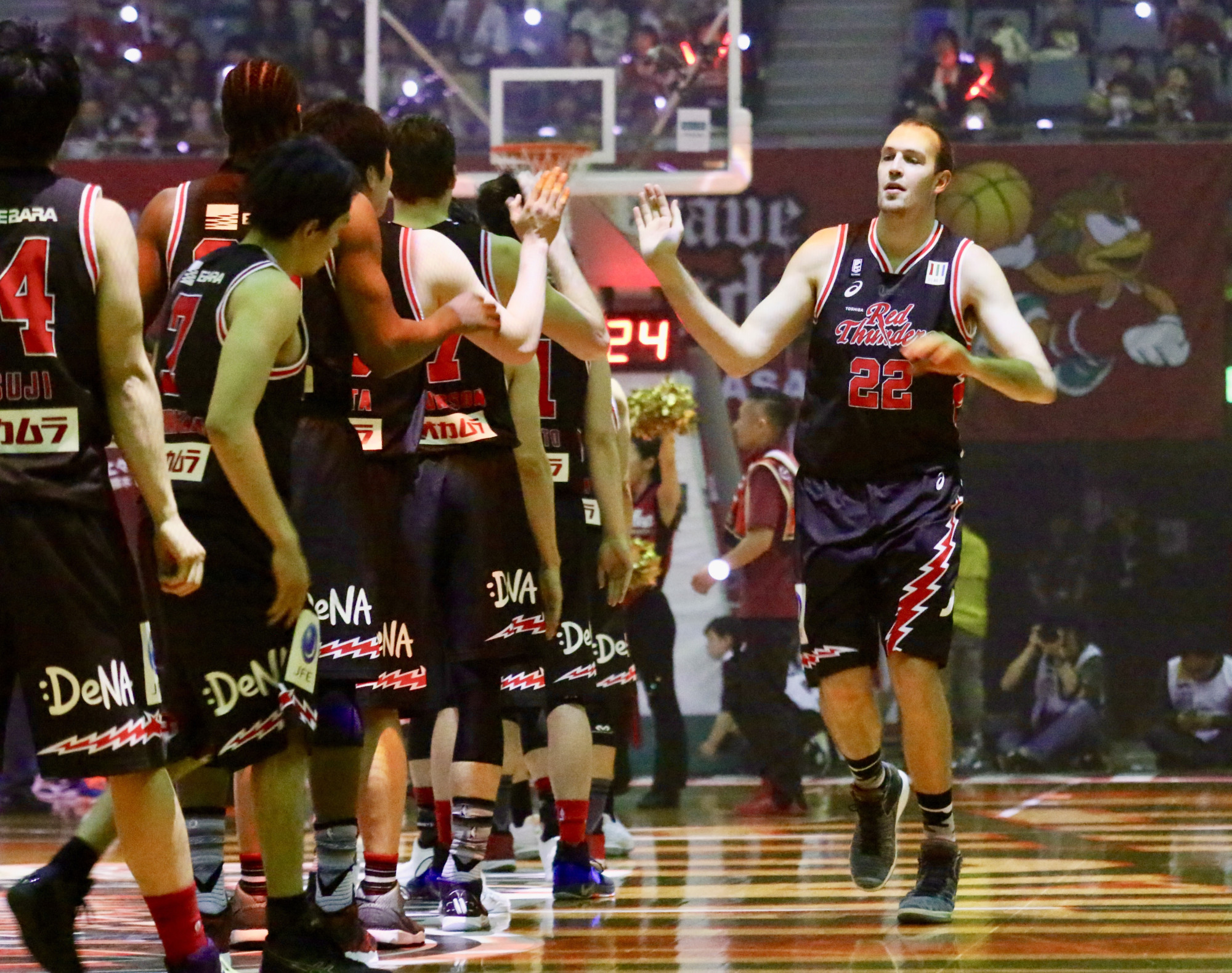 Kawasaki Brave Thunders center Nick Fazekas (22) high-fives his teammates before their final regular-season game at Todoroki Arena on Friday. The players wore throwback jerseys featuring the team's old nickname, Red Thunders, for the series against the Kyoto Hannaryz. | KAZ NAGATSUKA
