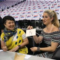 Nanae Yamano (left) watches as an American TV anchor shows one of Yamano's drawings to the camera at the Oklahoma City Thunder's Chesapeake Energy Arena last month. | NBAE/GETTY IMAGES