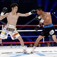 WBC light flyweight champion Ken Shiro (left) punches Mexican challenger  Ganigan Lopez in the first round of their title fight on Friday at Ota City General Gymnasium. | AP
