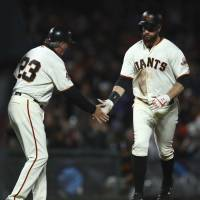 San Francisco's Brandon Belt is congratulated by third base coach Ron Wotus after hitting a home run against Cincinnati in the eighth inning on Monday night. | AP