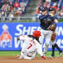 Atlanta's Dansby Swanson (right) throws to first base to force out Philadelphia's Maikel Franco on Tuesday.