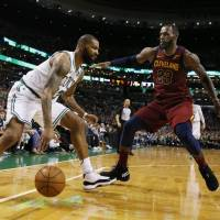 The Celtics' Marcus Morris (left) dribbles while being guarded by Cavaliers forward LeBron James during Game 1 of the Eastern Conference finals on Sunday in Boston. | AP