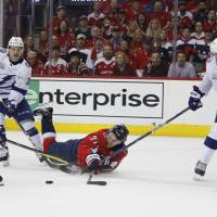Washington's T.J. Oshie falls onto the ice between Tampa Bay's Nikita Kucherov (left), Yanni Gourde (center) and Victor Hedman during the second period of Game 4 on Thursday night. | AP