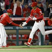 Shohei Ohtani is congratulated by Angels third base coach Dino Ebel after his home run during the ninth inning against the Rays on Thursday. | AP
