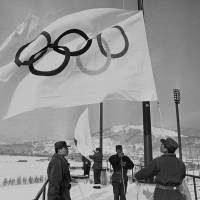 Members of Japan's Ground Self-Defense Force are seen raising Olympic flags in Sapporo in a file photo taken Jan. 23, 1972, before the opening of the 1972 Winter Games. | AP
