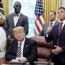 Actor Sylvester Stallone makes a boxing gesture while U.S. President Donald Trump sits after signing an executive order granting a posthumous pardon for Jack Johnson, the first black heavyweight boxing champion, in the Oval Office of the White House in Washington Thursday. Johnson was convicted of racially tinged federal morals charges more than a century ago.