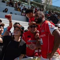 Fans at Hong Kong's Mong Kok Stadium take photos with the Sunwolves' Michael Leitch after the team's May 19 Super Rugby game against the Stormers. | AFP-JIJI