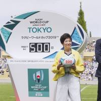 Rugby star Ayumu Goromaru (right) and Tokyo Governor Yuriko Koike (center) participate in an event marking 500 days to go until Rugby World Cup 2019 at Prince Chichibu Memorial Rugby Ground on Sunday. | KYODO