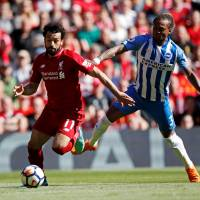 Liverpool forward Mohamed Salah (left) takes on Brighton's Gaetan Bong during their Premier League match at Anfield on Sunday. | ACTION IMAGES VIA REUTERS