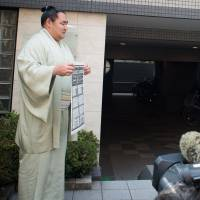 Yokozuna Kakuryu holds up a banzuke in front of photographers outside his stable in this April 24, 2014, file photo. | JOHN GUNNING