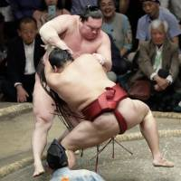Abi grapples with Hakuho (rear) on Friday in the Summer Grand Sumo Tournament at Ryogoku Kokugikan. Abi handed the yokozuna his first defeat of the 15-day tournament. | KYODO