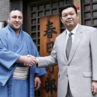 Tochinoshin (left) poses for photos with his stablemaster Kasugano on Monday. | KYODO