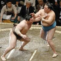 Yokozuna Hakuho (left) tussles with Tamawashi at the Summer Grand Sumo Tournament on Sunday. | KYODO
