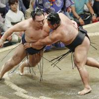 Shohozan (right) pushes out yokozuna Kakuryu to win their bout on Wednesday, the fourth day of the Summer Grand Sumo Tournament. | KYODO