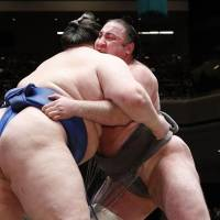 Tochinoshin (right) gets to grips with Ichinojo at the Summer Grand Sumo Tournament on Sunday. | KYODO