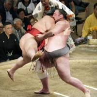 Tochinoshin (right) picks up Daieisho during their bout at the Summer Grand Sumo Tournament on Monday. | KYODO