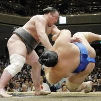Tochinoshin (left) defeats Kotoshogiku during their bout on the 11th day of the Summer Grand Sumo Tournament on Wednesday at Ryogoku Kokugikan. | KYODO