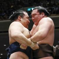 Kakuryu (left) and Hakuho compete during the final bout of the Summer Basho on Sunday at Ryogoku Kokugikan. Kakuryu defeated his yokozuna rival to clinch the title. | KYODO