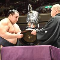 Kakuryu receives the trophy after winning the Summer Grand Sumo Tournament on Sunday. | KYODO