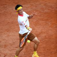 Kei Nishikori plays a shot from Grigor Dimitrov in their second-round match at the Italian Open on Wednesday. Nishikori won 6-7 (4-7), 7-5, 6-4. | REUTERS