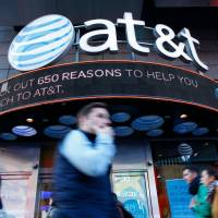 People walk past an AT&T store in New York in 2016. A US judge cleared the AT&T merger with Time Warner with no conditions on Tuesday. | AFP-JIJI