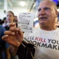 Professional odds-maker Stu Feiner holds up a betting slip for $5,000 Thursday after placing a bet at the Monmouth Park Sports Book on the first day of legal sports betting in the state, in Monmouth, New Jersey.   AFP-JIJI