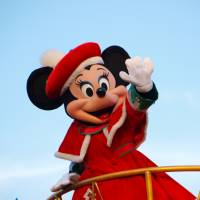 Minnie Mouse, wearing a red coat, waves during a daytime parade at Tokyo Disneyland in Urayasu, Chiba Prefecture, in December 2012. Under a special deregulation project, the prefecture is now considered a possible candidate to operate a casino resort complex. | GETTY IMAGES