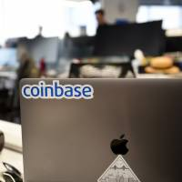 A Coinbase Inc. sticker is seen on a laptop computer at the company's office in San Francisco last Dec. 1. | BLOOMBERG