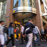 Pedestrians walk past a Commonwealth Bank of Australia branch in Sydney. | BLOOMBERG