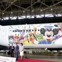 A Disney-themed Japan Airlines jet is seen on Friday at Haneda airport. | KYODO
