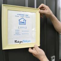 Masatada Suemitsu puts a sign on the door of his home in Nishitokyo, western Tokyo, on Friday, certifying that it is a registered private lodging. | KYODO