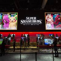 Attendees play Nintendo Co.'s Super Smash Bros. Ultimate at the company's booth during the E3 Electronic Entertainment Expo in Los Angeles on Tuesday. | BLOOMBERG