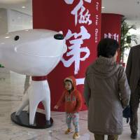 A child stands near the mascot for Chinese e-commerce giant JD.com and the words for 'Be Number One' at the headquarters in Beijing last November. Google said Monday it will invest $550 million in Alibaba's main rival, JD.com, as the U.S. tech giant seeks to expand in fast-growing Asian e-commerce markets. | AP