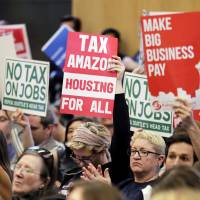 People attending a Seattle City Council meeting hold signs that read 'Tax Amazon, Housing for All' and 'No Tax on Jobs' as they listen to public comment on the debate over a possible council vote on whether or not to repeal a tax on large companies such as Amazon and Starbucks that was intended to combat a growing homelessness crisis, Tuesday at City Hall in Seattle.   AP